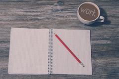 Top above close up view photo of Open notebook, pencil, cup of coffee with inscription `work` on it on grey wooden background, t. Op view. Tired after hard work royalty free stock photography