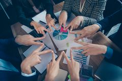 Top above high angle cropped close-up view of stylish sharks agent broker putting v-sign in round circle over desktop. Desk table charts diagram graph graphic royalty free stock photography
