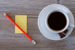 Top above overhead close up view photo of dark morning fresh tasty hot aromatic coffee espresso with foam yellow stickers paper fo. R writing making notes and Stock Image
