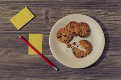 Top above overhead close up view photo picture of yummy tasty homemade cookies biscuits bitten on white round plate and yellow lis. Ts stockers for notes Stock Image