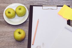 Top above overhead close up view photo of tasty healthy juicy green apples fruit note pad clipboad for making notes on wooden tabl royalty free stock photos