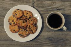 Top above overhead close up view photo of tasty yummy homemade delicious biscuits with chocolate on white eroud plate dark morning. Coffee isolated on wooden Stock Photo