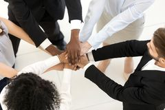 Top above view diverse business people stacked hands. Top above overhead view diverse multiracial business people standing putting their hands together starting stock photo