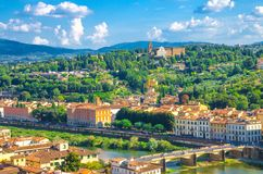 Top aerial panoramic view of green hills with Abbazia di San Miniato al Monte, bridges over Arno river, blue sky white clouds back royalty free stock image