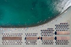 Top aerial view of the beach. Top aerial view of the pebble beach. Rows of umbrellas and sunbeds, warm blue sea and holiday makers having fun. Copy space royalty free stock photos