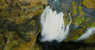Top aerial view of the beautiful Gljufrabui waterfall in iceland. Copter flying over flow of water falls down from cliff stock footage