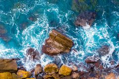 Top aerial view of blue waves crashing on rocky Australian coastline. Summer seascape with birds eye view shot over ocean waves and cliffs. Travel concept Royalty Free Stock Photography