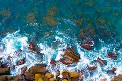 Top aerial view of blue waves crashing on rocky Australian coastline. Summer seascape with birds eye view shot over ocean waves and cliffs. Travel concept stock photos