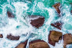 Top aerial view of blue waves crashing on rocky Australian coastline. Summer seascape with birds eye view shot over ocean waves and cliffs. Travel concept stock photography