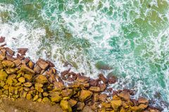 Top aerial view of blue waves crashing on rocky Australian coastline. Summer seascape with birds eye view shot over ocean waves and cliffs. Travel concept Royalty Free Stock Image