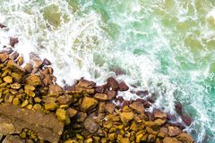 Top aerial view of blue waves crashing on rocky Australian coastline. Summer seascape with birds eye view shot over ocean waves and cliffs. Travel concept Stock Photo