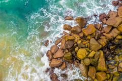 Top aerial view of blue waves crashing on rocky Australian coastline. Summer seascape with birds eye view shot over ocean waves and cliffs. Travel concept Royalty Free Stock Photo