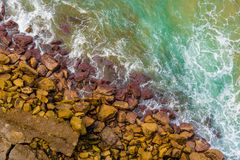 Top aerial view of blue waves crashing on rocky Australian coastline. Summer seascape with birds eye view shot over ocean waves and cliffs. Travel concept Stock Images
