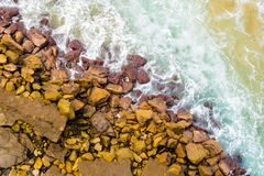 Top aerial view of blue waves crashing on rocky Australian coastline. Summer seascape with birds eye view shot over ocean waves and cliffs. Travel concept Royalty Free Stock Photos