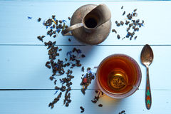 Top aerial view on desk with glass of tea, jug, tea leaves and teaspoon Stock Photo