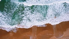 Top aerial view of foam waves break on orange colored sand beach. Bird`s eye view of emerald green blue ocean water stock video footage