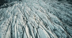 Top aerial view of ice valley in Iceland national park. Drone flying over white glacier Vatnajokull with volcanic ash stock video