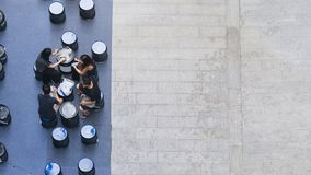 Top aerial view of people sit and talk picnic in pedestrian street. The top aerial view of people sit and talk picnic in pedestrian street Royalty Free Stock Photos