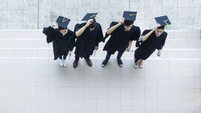 Top aerial view of people students in the feeling of happy. And graceful with the graduation gowns throw up the cap stock photography
