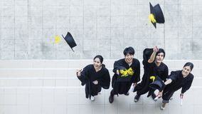 Top aerial view of people students in the feeling of happy. And graceful with the graduation gowns and cap stand in the line at outdoor space royalty free stock image