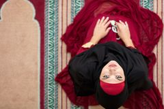 Top aerial view Young beautiful Muslim Woman Praying In Mosque.  Stock Images
