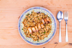 Top angle view on delicious Chinese spicy fried rice with roast pork on plate. Delicious Chinese spicy fried rice with roast pork in plate served on wooden table Royalty Free Stock Photography