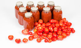 Top Angled View of Tomatoes with Tomato Sauce Jars. An Angled front studio view of some field tomatoes in front of canned jars of tomato homemade sauce Stock Images