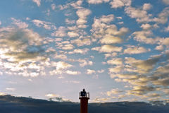 Top of beacon on a blue cloudy sky background. Sunset on Baltic sea.  Stock Photo