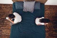 Top beskådar Barnparet sitter med baksidor till varandra på olika kanter av säng Arkivbilder