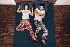 Top beskådar Den unga kvinnan snarkar högt och förhindrar den irriterade mannen från att sova arkivbild