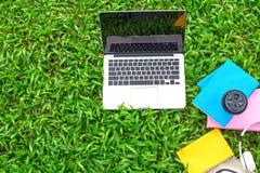 Top beskådar Enjoy lyssnande musik med koppkaffe på gräsfältet av parkera i morgonen arkivbilder