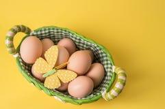 Top beskådar Lantliga ägg i en vide- korg som fodras med rutigt tyg r Gul bakgrund kopia royaltyfri bild