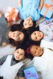Top beskådar Stående av lyckliga barn som ligger på golv i form av cirkeln arkivbilder