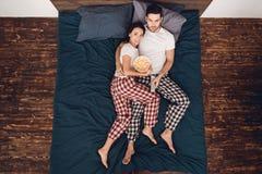 Top beskådar Unga härliga par ligger i pyjamas och klockafilm, medan äta popcorn arkivbilder