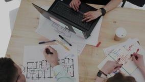Top besk?dar En grupp av unga fokuserade formgivare skapar plan av modern m?ng--v?ning ett bostads- komplex Kvinnligt r?cka stock video
