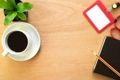 Top besk?dar Kaffe, bok, blyertspenna, anställdkort och trädkruka på det bruna träskrivbordet royaltyfria bilder