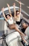 Top beskådar av kvinnor i cabrioleten med deras räcker upp Arkivbild