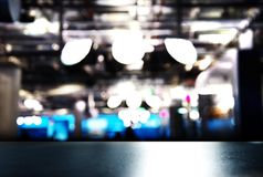 Top of black table counter  with blue silver modern lamp light i. N bar pub or club at night background Royalty Free Stock Photo