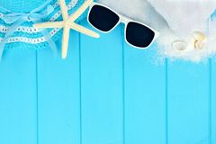 Top border of beach items and seashells on blue wood Stock Image