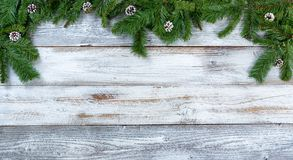 Top border of Christmas fir branches and pine cones on rustic wh. Top border of Christmas tree fir branches and pine cones on rustic wood in flat lay format Royalty Free Stock Photos