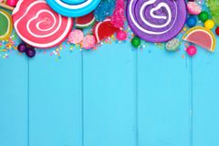 Top border of colorful assorted candies against blue wood. Top border of assorted colorful candies against a blue wood background Stock Photo