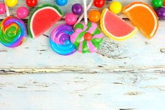 Top border of colorful candies against rustic wood. Top border of varied colorful candies against a rustic wooden background Stock Photography