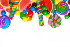 Top border of colorful candies over white. Top border of an assortment of colorful candies against a white background Royalty Free Stock Photos