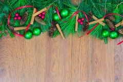 A top border of greenery with pine cones, cinnamon sticks, green ornaments, red berry clusters, and red ribbon. A top border of white pine, tamarack, and spruce royalty free stock photo