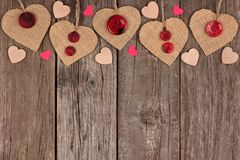 Top border of Valentines burlap hearts over rustic wood Stock Photography