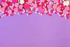 Top border of Valentines Day sweets and candy over purple Stock Photo