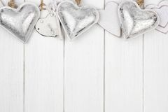 Top border of white and silver hearts on white wood Stock Image