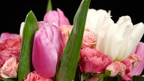 Top of bouquet flower with roses and tulips, on black, rotation stock video footage