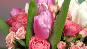 Top of bouquet flower with roses and tulips, on red, green, rotation, close up stock footage