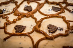 Top of a brown sweet cake with little chocolate hearts.  royalty free stock photos